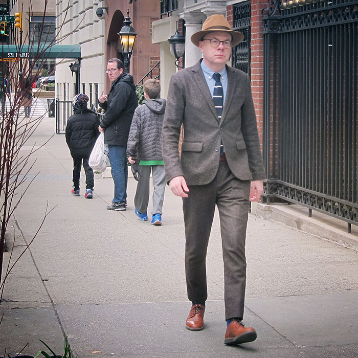 the author walking down the street in a suit, people turning and looking