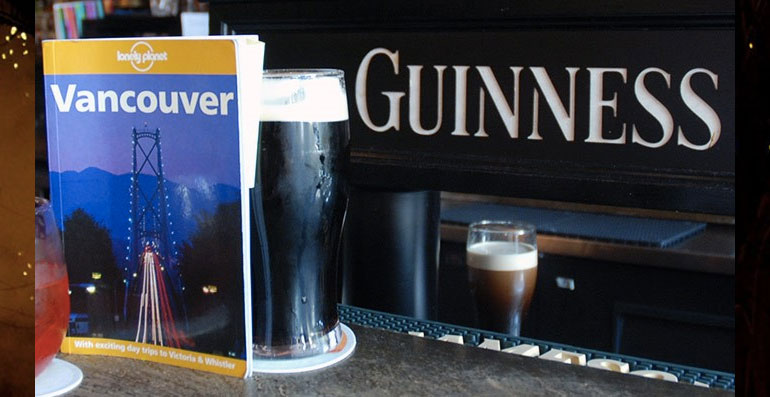 The vancouver guidebook beside a glass of beer