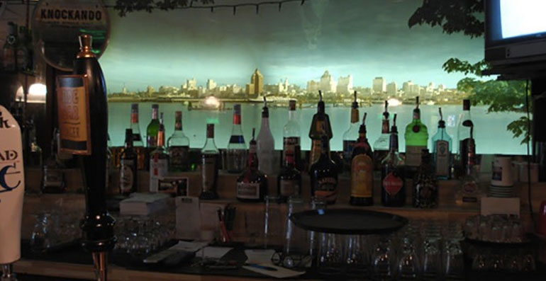Interior shot of the side bar lounge's lit up shot of vancouver harbour with bottles in front of it