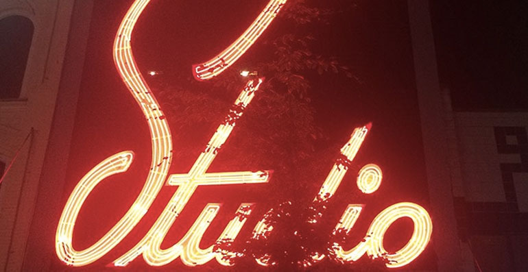 Neon lit up sign with the wordmark Studio
