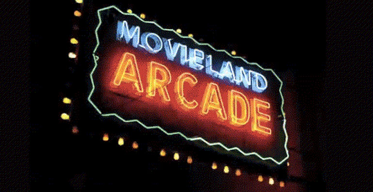 Lit up neon sign with the words Movieland Arcade