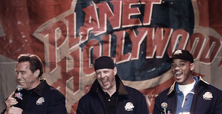 Arnold S, Bruce Willis and Will Smith standing in front of the Planet Hollywood Marquee during it's opening celebration