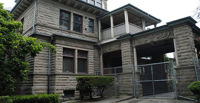 exterior of the rogers mansion with a chainlink fence around it