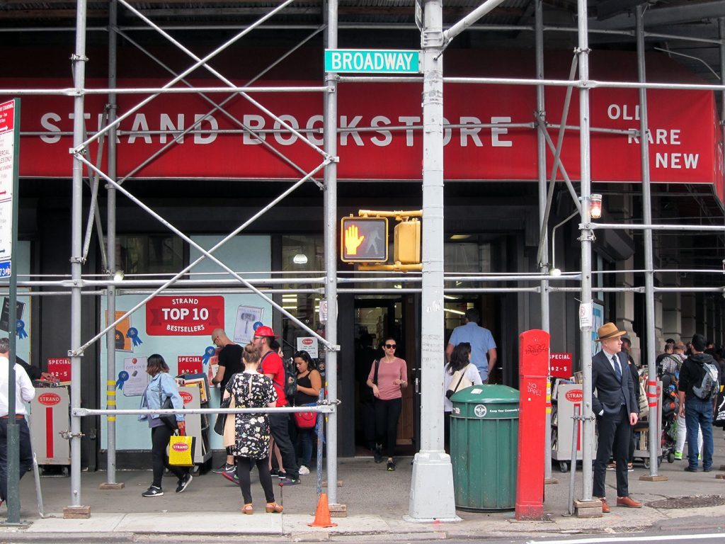 the author in a suit standing outside the strand bookstore under scaffolding